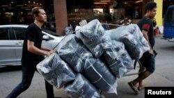 푸미폰 아둔야뎃 국왕 서거 이후 태국 전역에서 검은색과 흰색 상복이 품귀현상을 빚고 있는 가운데, 지난 15일 수도 방콕 상인들이 검정 티셔츠를 배송하고 있다.