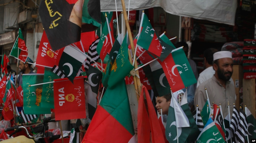 Flags of political parties are on sale ahead of elections, in Peshawar, Pakistan, Friday, July 20, 2018.