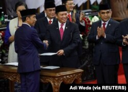 Presiden RI Joko Widodo disambut Ketua Majelis Permusyawaratan Rakyat Bambang Soesatyo seusai pengambilan sumpah saat pelantikan presiden periode kedua, di Gedung DPR, Jakarta, 20 Oktober 2019. (Foto: Adi Weda via REUTERS)