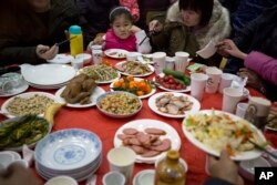 "A Chinese girl looks upon a table full of food during a ""1,000 people dumpling feast"" in Liuminying village on the outskirt of Beijing, China, Jan. 27, 2017."