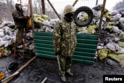 Ukrainian anti-government protesters stand near a passage in a barricade at the site of recent clashes with riot police in Kyiv, Feb. 17, 2014.