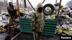 2月17号乌克兰抗议者站在基辅与防暴警察最近发生冲突地点的一个路障的通道附近