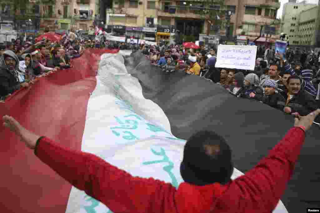 2013年2月1日,在开罗解放广场的礼拜五祷告之后,一名反穆尔西的示威者(中)向舞动一面巨大埃及国旗的示威者打手势。