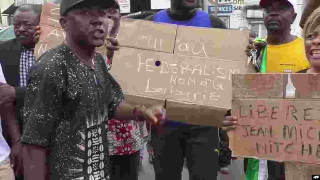 Watu walojitokeza na mabango kwa ajili ya maandamano mjini Douala, 21 octobre 2017.