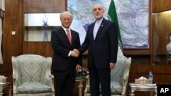 지난 9월 이란 테란을 방문한 아마노 유키야 국제원자력기구 사무총장(왼쪽)이 알리 아크바르 살레히 이란 원자력청장을 만나 악수하고 있다. (자료사진)