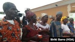 Des bénéficiaires ayant reçu leur kit composé d'un téléphone portable. (VOA/ Siriki Barro)