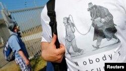 """Seorang pengunjuk rasa menentang NSA dan memberikan dukungan kepada Edward Snowden dengan berdiri di luar wilayah yang dijuluki """"Dagger Complex"""", basis intelijen Angkatan Darat AS di Griesheim, Jerman, 20 Juli 2013 (Foto: dok)."""