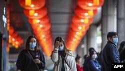 Pedestrians wear face masks as they walk outside the New Orient Landmark hotel in Macau.