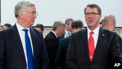 U.S. Secretary of Defense Ashton Carter, right, speaks with British Secretary of State for Defense Michael Fallon at the start of a meeting at EU headquarters in Brussels, June 24, 2015.