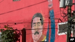 FILE - A mural of Venezuela's President Nicolas Maduro can be seen on the wall of a house in the popular neighborhood of Petare in Caracas, Venezuela.
