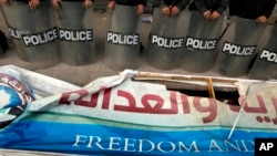 FILE - Egyptian anti-riot soldiers stand guard in front of a destroyed banner of the Muslim Brotherhood's Freedom and Justice Party, March 2013.