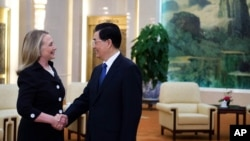 Clinton, left, shakes hands with Chinese President Hu Jintao during a bilateral meeting at the Great Hall of the People in Beijing, Sept. 5, 2012.