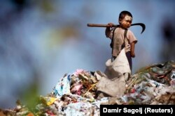 An illegal immigrant boy from Myanmar collects plastic at a rubbish dump near Mae Sot December 22, 2009.
