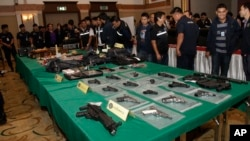 FILE - Thai police officials display seized guns before a press conference in Bangkok, Thailand, Oct. 28, 2015.