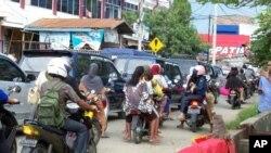 ພວກປະຊາຊົນຂີ່ລົດຈັກພາກັນ ຟ້າວພາກັນໄປລີ້ໄພໃນທີ່ດິນສູງ ຫຼັງຈາກແຜ່ນດິນໄຫວໃນແຂວງ Aceh ອິນໂດເນເຊຍ. ວັນທີ 11 ເມສາ 2012.