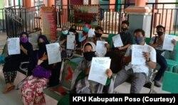 Sejumlah anggota PPS berfoto bersama sambil memperlihatkan hasil tes cepat (rapid test) Covid-19 dengan hasil non-reaktif di salah satu puskesmas di Poso Kota, Kabupaten Poso, Sulawesi Tengah, 25 Juni 2020. (Foto: KPU Kabupaten Poso)
