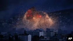 Cảnh tượng sau một trận không kích của liên minh do Mỹ dẫn đầu tại Kobani, Syria, tháng 10/2014. Quân đội Syria được đặt trong tình trạng báo động về khả năng một trận không kích của Mỹ có thể xảy ra sau khi chính quyền TT Bashar al-Assad bị cáo buộc tấn công bằng vũ khí hóa học vào thường dân.
