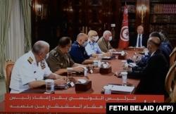 Le président tunisien Kais Saied annonce la dissolution du parlement et du gouvernement du Premier ministre Mechichi alors qu'il est assis avec son état-major militaire le 25 juillet 2021 au Palais de Carthage. (Capture d'écran de la télévision)