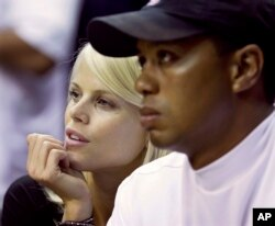 FILE - Elin Nordegren talks to her husband, golfer Tiger Woods, during the first quarter of Game 4 of the NBA basketball finals in Orlando, Florida, June 11, 2009.