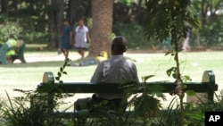 FILE - A man sits on a bench in a park in Harare, Zimbabwe, March 26, 2014. Zimbabwe has taken a new approach to addressing mental health issues by installing 'friendship benches' for counseling sessions.