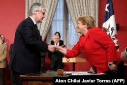 Chile's new finance minister, Nicolas Eyzaguirre (L), shakes hands with President Michelle Bachelet at La Moneda Presidential Palace in Santiago, Aug. 31, 2017.