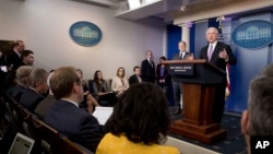 Attorney General Jeff Sessions, right, accompanied by White House press secretary Sean Spicer, second from right, talks to the media during the daily press briefing at the White House in Washington, Monday, March 27, 2017.