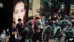 یکم اکتوبر کو چین کے قومی دن کے موقع پر پولیس اہلکار ہانگ کانگ کے ایک بس اسٹاپ پر کھڑے مسافروں کو چیک کر رہے ہیں۔