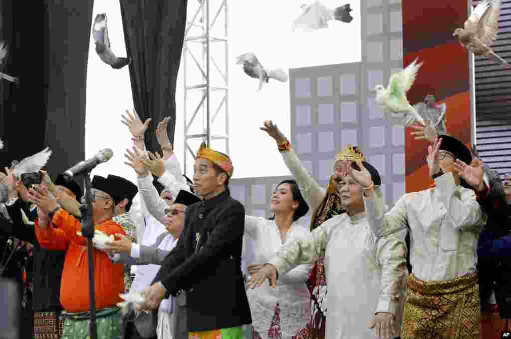 លោកប្រធានាធិបតីឥណ្ឌូណេស៊ី Joko Widodo (រូបឆ្វេងទី២) និងដៃគូឈរឈ្មោះបោះឆ្នោតជាមួយលោកគឺ លោក Ma'ruf Amin (រូបឆ្វេង) និងលោក Prabowo Subianto (រូបស្តាំទី២) ដែលជាគូប្រជែងនឹងលោក Joko Widodo និងលោក Sandiaga Uno (រូបស្តាំ) ដែលដៃគូឈរឈ្មោះបោះឆ្នោតជាមួយនឹងលោក Prabowo Subianto ប្រលែងបក្សីនៅក្នុងពិធីមួយសម្រាប់ការចាប់ផ្តើមយុទ្ធនាការសម្រាប់ការបោះឆ្នោតនៅឆ្នាំក្រោយ ក្នុងក្រុងហ្សាការតា។