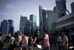 FILE - People walk across a main street in the financial district of Singapore.