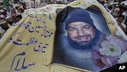 Kelompok Islam garis keras Pakistan membawa poster Mumtaz Qadri dalam unjuk rasa di Karachi untuk menentang hukuman mati yang dijatuhkan oleh pengadilan Pakistan (foto: dok).