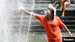 Seorang pria memanfaatkan air mancur untuk mendinginkan diri di hari yang panas di Manhattan, New York, Sabtu (23/7).