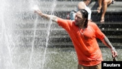 A man enjoys a cooling spray from a fountain during a heat wave in Manhattan, New York, July 23, 2016.