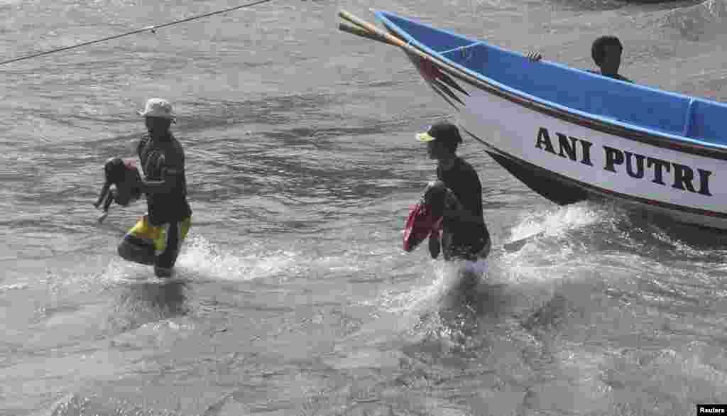 Para nelayan membawa jenazah anak-anak yang menumpang kapal berisi pencari suaka yang terbalik akibat menghantam karang (24/7).