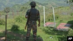 FILE- Indian army soldier guards near fence on the line of control near Balakot sector in Poonch, Jammu and Kashmir, India, Aug.17, 2015.