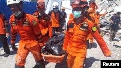 Tim SAR membawa korban dari reruntuhan Hotel Roa-Roa di Palu, Sulawesi Tengah, 30 September 2018.
