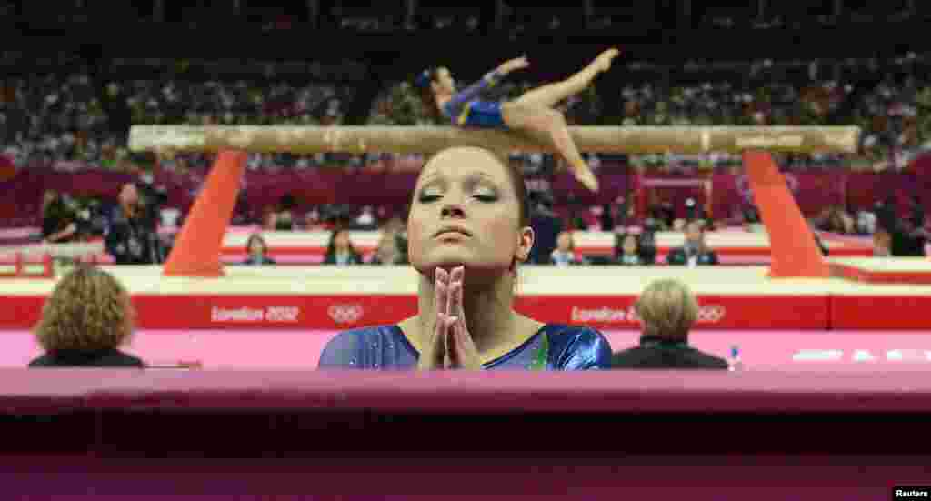 Ethiene Cristina Gonser Franco of Brazil (C) prays whilst teammate Harumy Mariko de Freitas performs on the balance beam during the women's gymnastics qualification at the North Greenwich Arena during the London 2012 Olympic Games July 29, 2012.