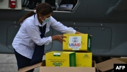 A government employee receives diagnostic testing kits donated by the United States Agency for International Development (USAID).