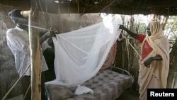 Ana taimakawa wata mace a Sudan ta makala gidan sauro.