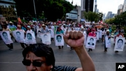 FILE -Relatives of the 43 missing students from the Isidro Burgos rural teachers college march holding pictures of their missing loved ones during a protest in Mexico City, July 26, 2015.