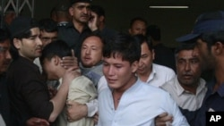 People comfort youths who lost their family members in a shooting in Quetta, Pakistan on Sept 20, 2011.