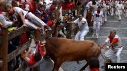 Seseorang ditanduk oleh banteng petarung dalam festival San Fermin di Pamplona, Spanyol, Juli 2014.