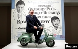 "Audrey Hepburn's son, Sean Hepburn Ferrer, poses on the Vespa scooter his mother rode on in the 1953 movie ""Roman Holiday"" at the exhibition ""Intimate Audrey"" in Brussels, Belgium, May 2, 2019. (REUTERS/Francois Lenoir)"