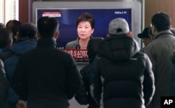 People watch a live broadcast of South Korean President Park Geun-hye addressing the nation at the Seoul Railway Station in Seoul, South Korea, Nov. 29, 2016.