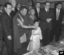 1996年1月12日,中国官方选择的六岁的11世班禅喇嘛向中国主席江泽民呈现给他的礼品。中国政协主席李瑞环在场。