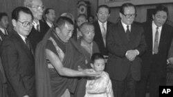 1996年1月12日,中方选择的六岁的11世班禅喇嘛向中国主席江泽民呈现给他的礼品。中国政协主席李瑞环在场。