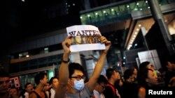 Sinh viên biểu tình ủng hộ dân chủ cầm biểu ngữ với hình ảnh một người biểu tình bị cảnh sát đánh đập tại quận Wan Chai ở Hồng Kông.