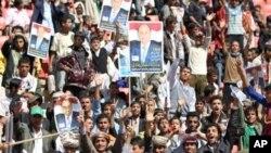 在也门首都萨那2月20日举行的选举集会上,民众手持副总统哈迪肖像的标语牌