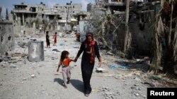 Phụ nữ Palestine dắt con đi ngang những tòa nhà bị phá hủy khi trở về thị trấn Beit Hanoun sau các vụ không kích của Israel, ngày 5/7/2014.