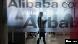 Employee seen behind glass door of Alibaba's company headquarters on the outskirts of Hangzhou, China, April 23, 2014.