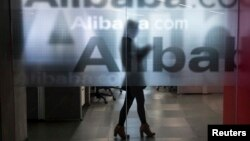 Employee seen behind glass door of Alibaba's company headquarters on the outskirts of Hangzhou, Zhejiang province, April 23, 2014.